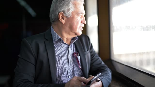 Mature Businessman Looking Through Window and Dreaming