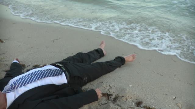 vídeos de stock e filmes b-roll de slo mo ms mature businessman lying on beach at water's edge, low section, miami beach, florida, usa - water's edge