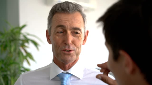 Mature businessman sharing ideas with colleague