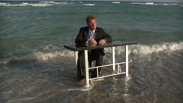 slo mo ws mature businessman sitting at desk in ocean waves, miami beach, florida, usa - kostym bildbanksvideor och videomaterial från bakom kulisserna
