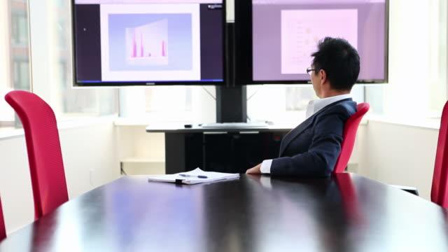 vídeos de stock e filmes b-roll de ms tu mature businessman sitting in conference room looking at graphs on monitor rear view/seattle, washington, usa - vestuário de trabalho formal