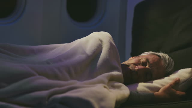 mature businessman sleeping in private airplane - blanket stock videos & royalty-free footage
