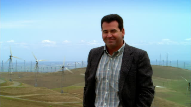 MS Mature businessman standing near wind turbines on hillside / Livermore, California, USA