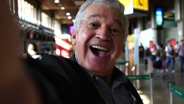 mature businessman taking a selfie on airport - mature men stock videos & royalty-free footage