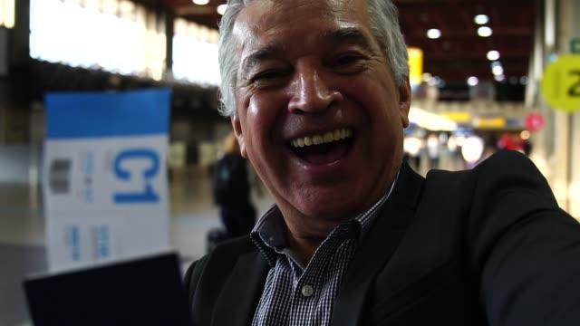 空港で、selfie を取って成熟したビジネスマン - パスポート点の映像素材/bロール