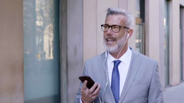 mature businessman talking on mobile phone in city - in ear headphones stock videos & royalty-free footage