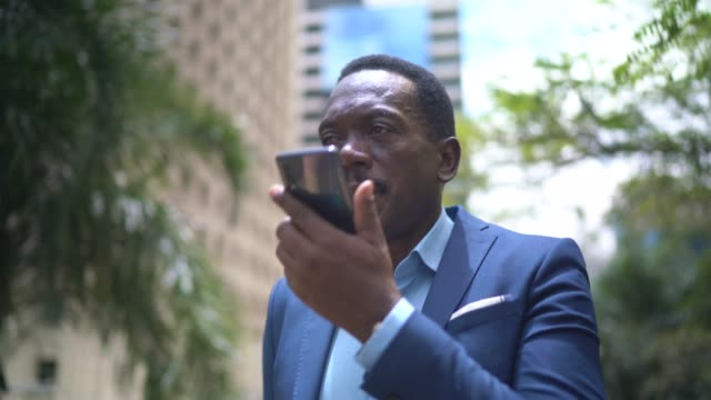 vídeos de stock e filmes b-roll de mature businessman talking on mobile phone while walking on the city - ditado