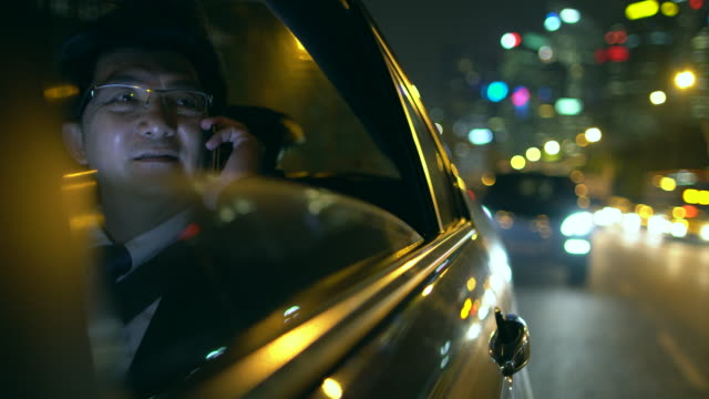 MS Mature businessman talking on phone in car at night