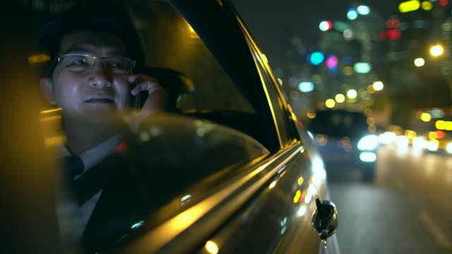 ms mature businessman talking on phone in car at night - sydostasien bildbanksvideor och videomaterial från bakom kulisserna