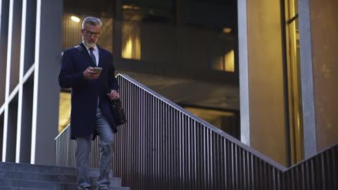mogen affärsman med mobiltelefon efter jobbet - 50 54 år bildbanksvideor och videomaterial från bakom kulisserna
