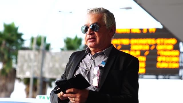 vídeos de stock e filmes b-roll de mature businessman using mobile phone at airport - mobile phone