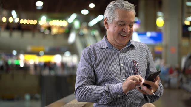 Mature Businessman Using Mobile Phone at Airport