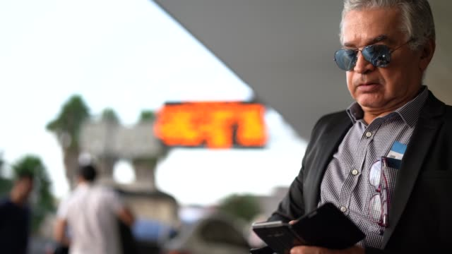 vídeos de stock e filmes b-roll de mature businessman using mobile phone at airport - 65 69 anos