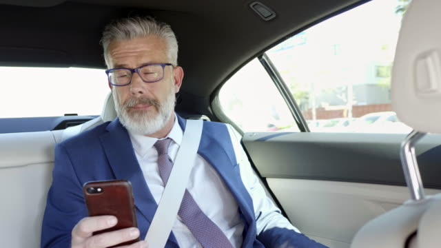 mature businessman using mobile phone in car - image stock videos & royalty-free footage