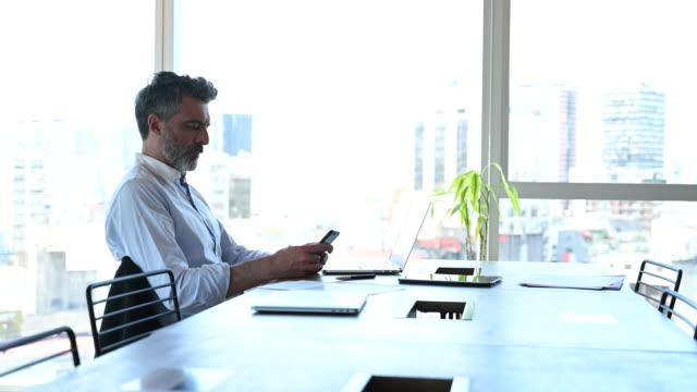 vídeos de stock, filmes e b-roll de empresário maduro usando telefone inteligente na mesa de conferência - só um homem