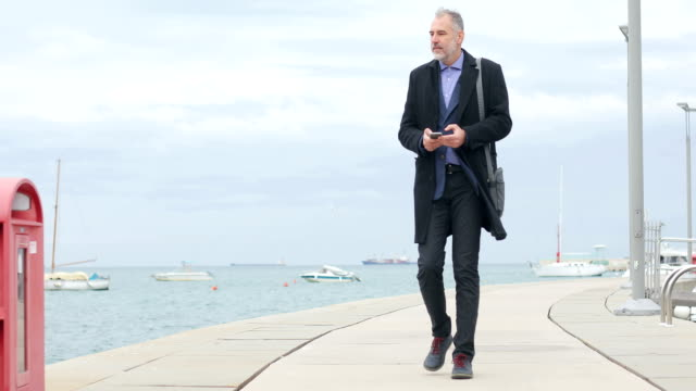 Mature Businessman Walking on a Pier and Using Mobile Phone