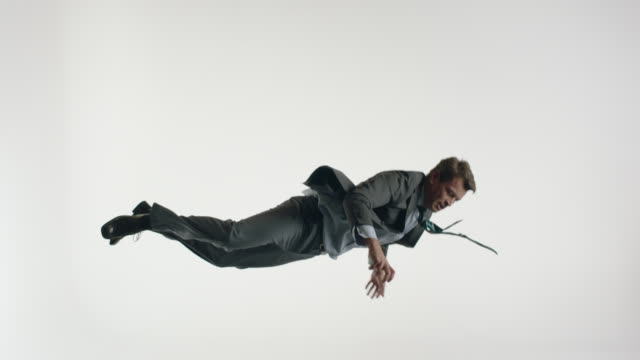 mature businessman wearing suit and tie, doing acrobatics in the air - white background stock videos & royalty-free footage