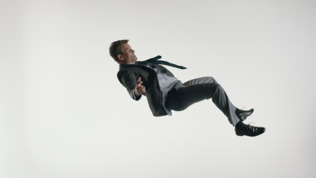 vidéos et rushes de mature businessman wearing suit and tie, doing acrobatics in the air - se déplacer vers le bas