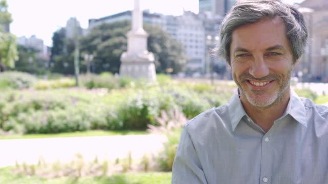 reife geschäftsmann mit grauen haaren im park an schönen tag - handsome people stock-videos und b-roll-filmmaterial