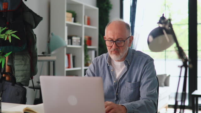 mature businessman working at home using lap top and smart phone - senior men stock videos & royalty-free footage