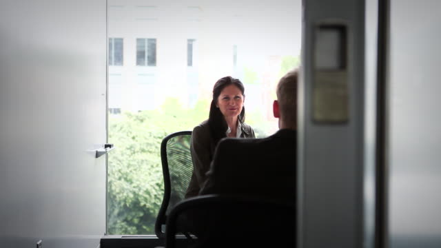 ms pan mature businesswoman and businessman in discussion in conference room/seattle, washington, usa - mitarbeiterengagement stock-videos und b-roll-filmmaterial