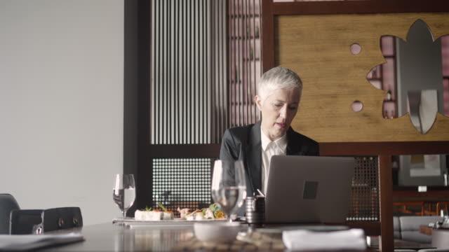 4 k : ältere geschäftsfrau essen und wokring im restaurant. - kurzes haar stock-videos und b-roll-filmmaterial