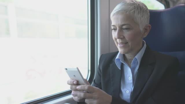 mature businesswoman in train - dentro video stock e b–roll