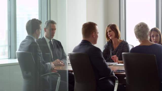 ms mature businesswoman leading discussion during meeting with colleagues in office conference room - board room stock videos and b-roll footage
