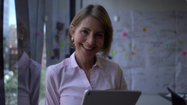 mature businesswoman leaning against office window looking at tablet and then facing camera smiling - zoom in stock videos & royalty-free footage