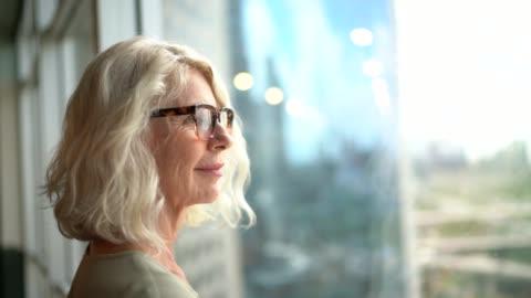 mogen affärskvinna tittar ut genom fönstret - planering bildbanksvideor och videomaterial från bakom kulisserna