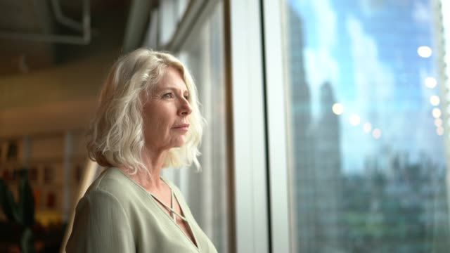 mature businesswoman looking out of window - white collar worker stock videos & royalty-free footage