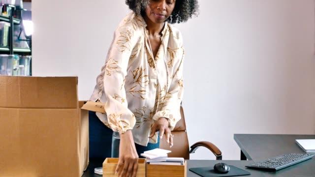 vídeos de stock e filmes b-roll de mature businesswoman packs up her things after losing her job during the covid-19 crisis. - trabalhadora de colarinho branco