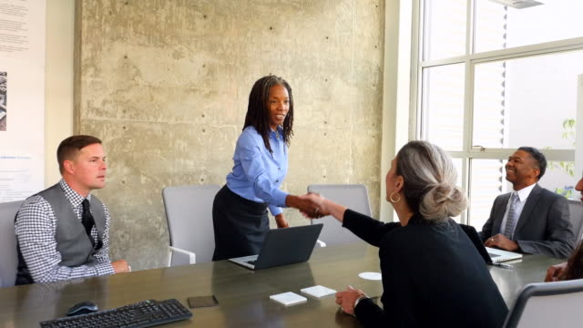 stockvideo's en b-roll-footage met ms ts mature businesswoman shaking hands with group of businesspeople during meeting in conference room in office - zakenvrouw