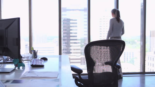 MS R/F mature businesswoman standing near window in office looking out