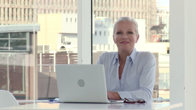 mature businesswoman using laptop in office - geschäftsfrau stock-videos und b-roll-filmmaterial