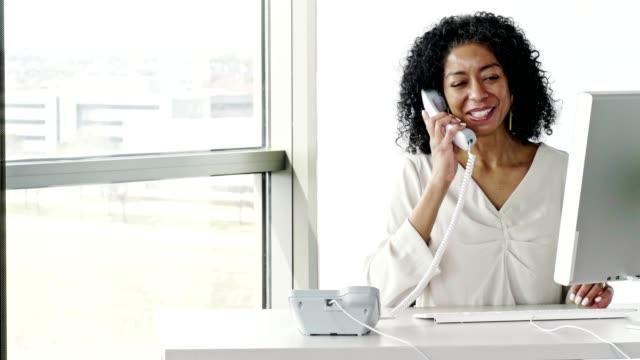 mature businesswoman using phone at her desk - landline phone stock videos & royalty-free footage