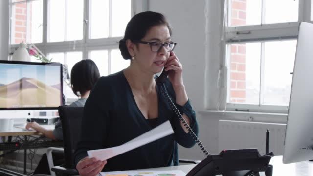 vídeos y material grabado en eventos de stock de mujer de negocios madura trabajando en su escritorio - teléfono con cable