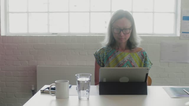 Mature businesswoman working at laptop in office