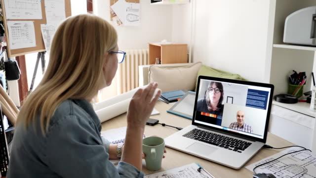 reife geschäftsfrau arbeitet von zu hause aus und macht videoanrufe mit mitarbeitern - instant messaging stock-videos und b-roll-filmmaterial
