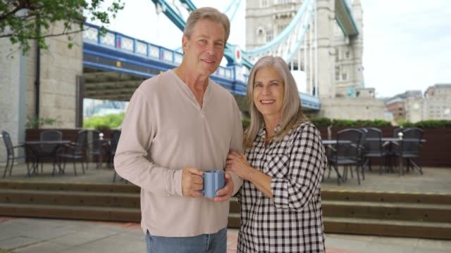 mature caucasian couple in love enjoy themselves at tower bridge - weitere themen stock-videos und b-roll-filmmaterial