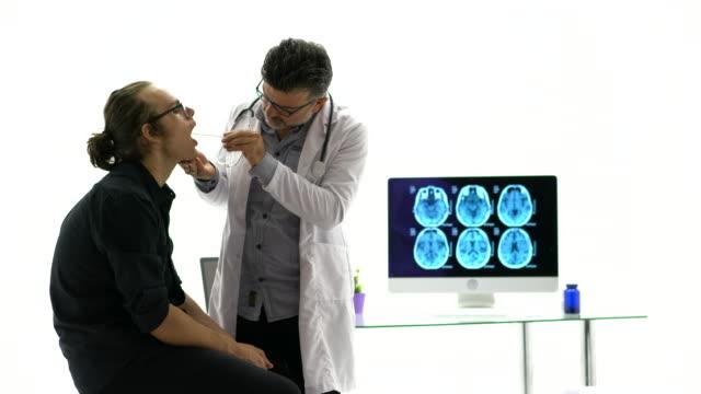 vídeos de stock, filmes e b-roll de doutor caucasiano maduro que examina a garganta do paciente no hospital. - bronquite