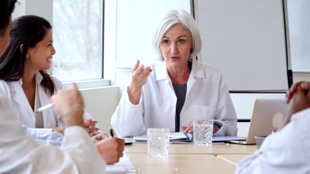 mature caucasian female doctor leads medical staff meeting - administrator stock videos and b-roll footage