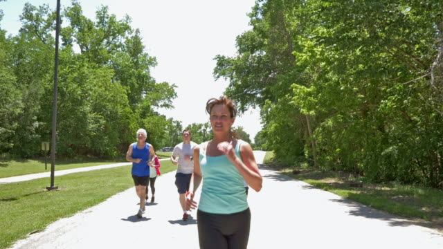 Mature Caucasian female fitness instructor leading group of runners during workout