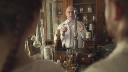 Mature Caucasian man standing at the table with vintage flasks, test tubes, vintage weighting machine, and talking. Senior guide working in retro pharmacy museum. Shooting over shoulder.