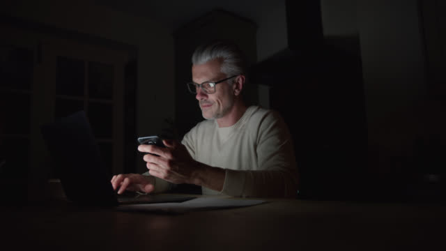 mature caucasian man working late at home using smartphone and laptop - urgency stock videos & royalty-free footage