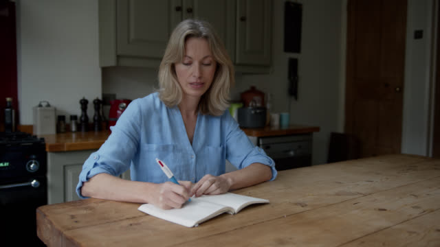 mature caucasian woman at home writing on her journal - diary stock videos & royalty-free footage
