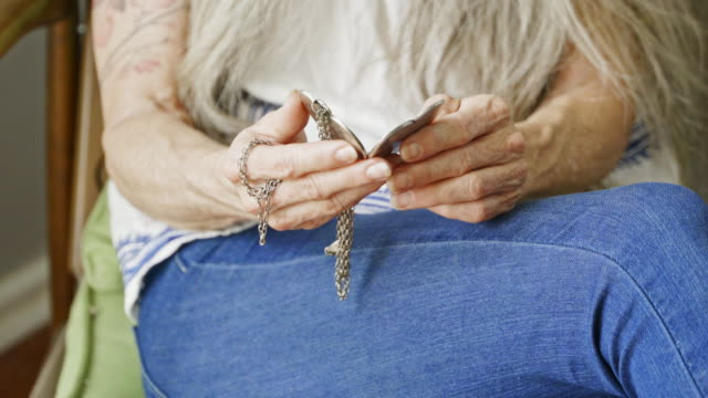 Mature Caucasian woman looking at photograph in heart-shaped silver locket