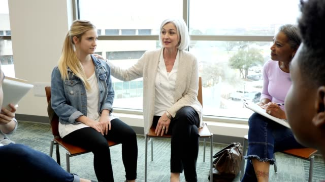 Mature Caucasian woman participates in support group with granddaughter