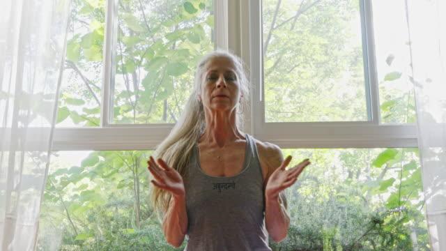 Mature Caucasian woman practicing yoga in livingroom