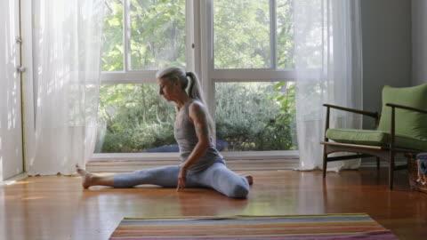 mature caucasian woman practicing yoga on livingroom floor - mature women stock-videos und b-roll-filmmaterial